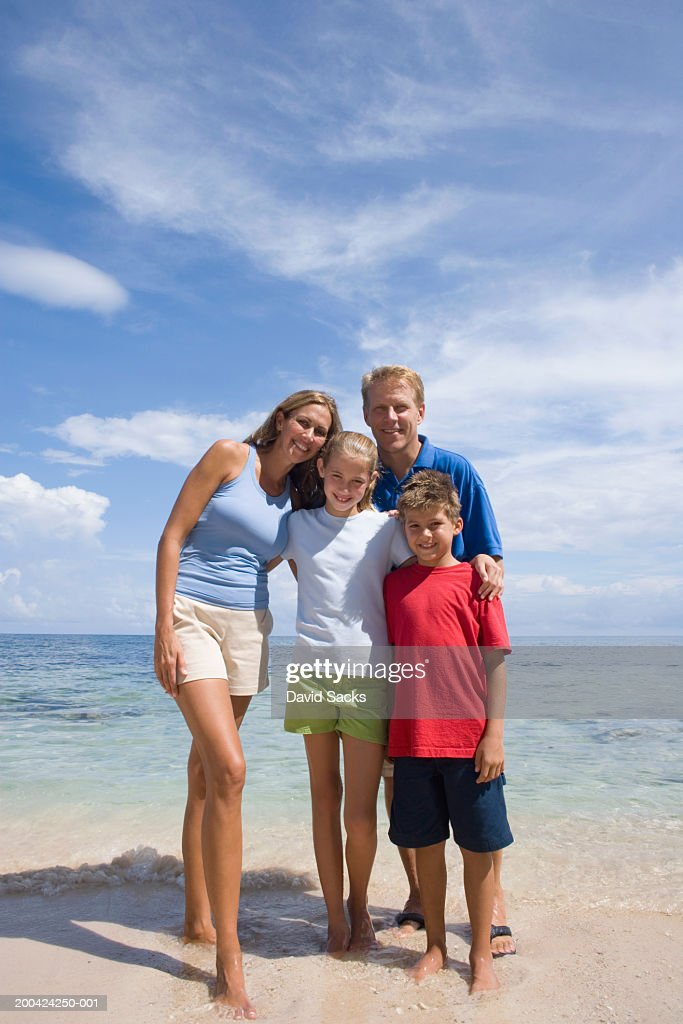 Parents with children (10-12) on beach smiling, portrait : Stock Photo