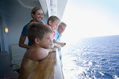 Parents with children (10-12) on cruise ship looking at ocean