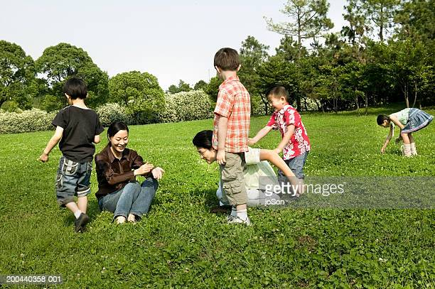 Parents with children (6-8) playing on grass