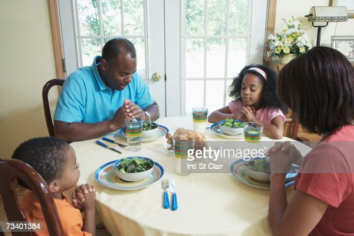 Parents With Children Praying At Dinner Table Stock Photo ...