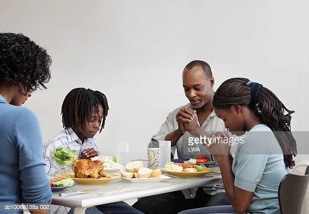 Parents with children (10-13) praying at table