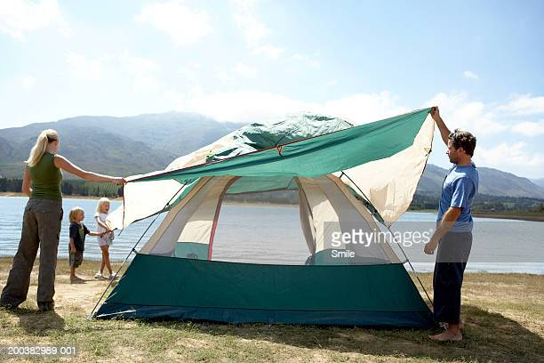 Parents with children (3-6) putting up tent near lake