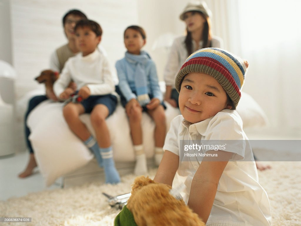 Parents with children (3-7) sitting in bedroom, focus on girl : Stock Photo