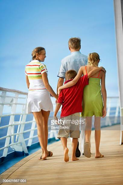 Parents with children (10-12) walking on cruise ship, rear view