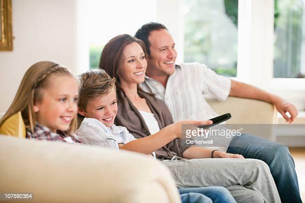 Os pais com crianças (8- 11) ver televisão em casa