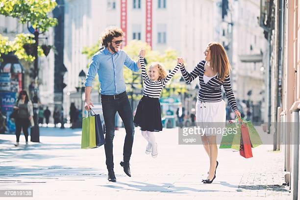 Eltern mit niedlichen kleinen Mädchen Genießen Sie die Einkaufsmöglichkeiten zusammen.
