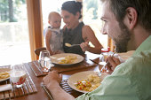 Parents with daughter (9-12 months) eating at dining table, focus on father