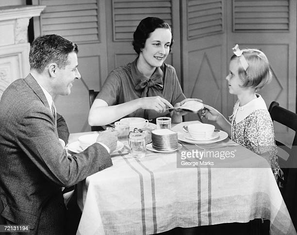 Parents with daughter (8-9) eating breakfast at home (B&W)