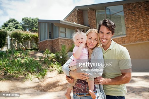 Parents with daughter (12-23 months) in front of house : Stock Photo