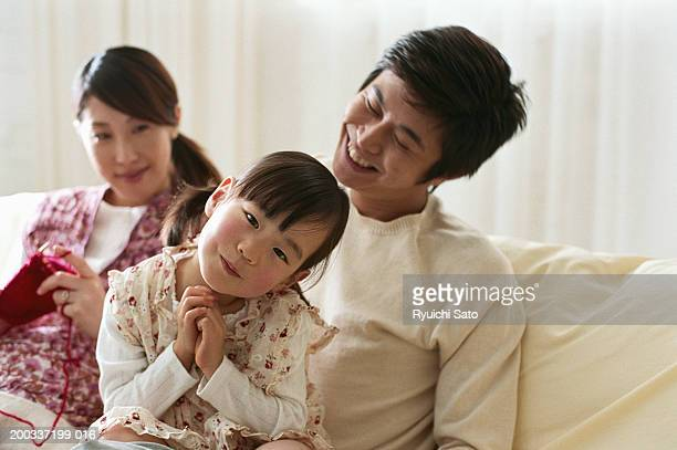 Parents with daughter (4-5) on sofa, woman knitting, smiling