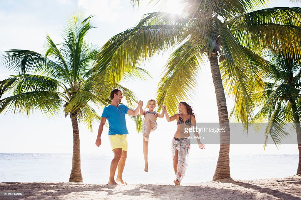 Parents with daughter (10-11) playing on beach : Stock Photo