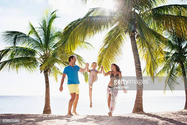 Parents with daughter (10-11) playing on beach