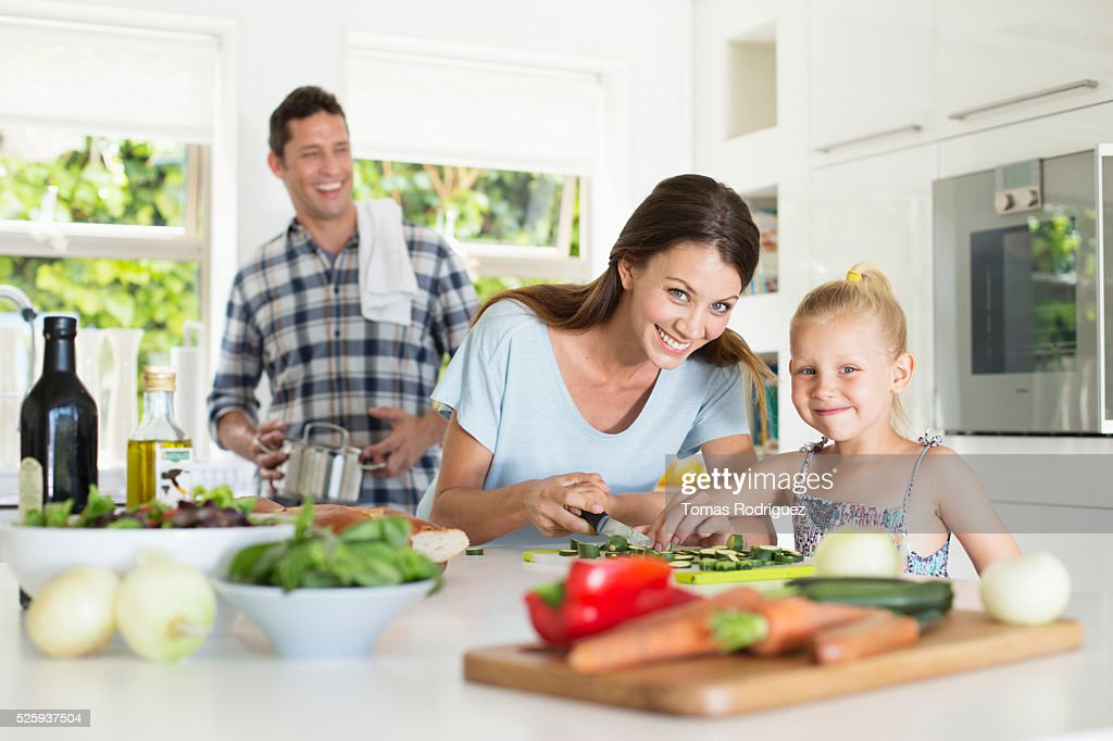 Parents with daughter (4-5) preparing food in kitchen : Stock Photo