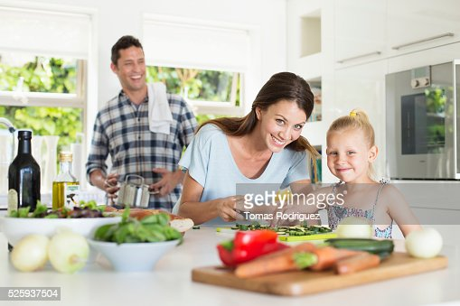 Parents with daughter (4-5) preparing food in kitchen : ストックフォト