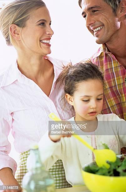 Parents with daughter (6-7) preparing salad