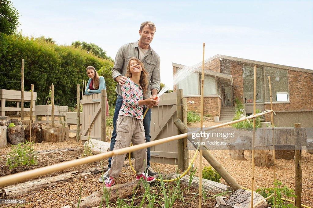 Parents with daughter (8-9) watering vegetable garden : Stock Photo