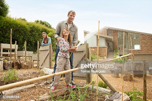 Parents with daughter (8-9) watering vegetable garden : Stock Photo