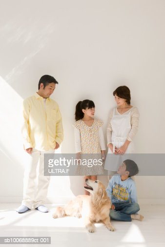 Parents with girl and boy (8-11) standing in room with dog : Stock Photo