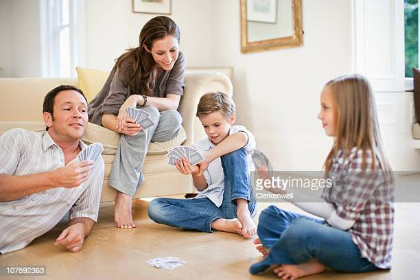 Parents with kids (8-11) playing cards in living room