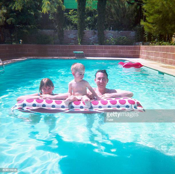 Parents with little son at airbed in swimming pool