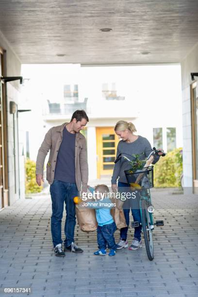 Parents with small boy walking after shopping