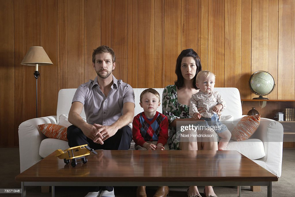 Parents with son (3-5), and baby girl (6-9 months) sitting on couch in living room : Stock Photo