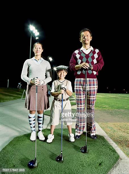 Parents with son (6-8) at golf driving range, portrait