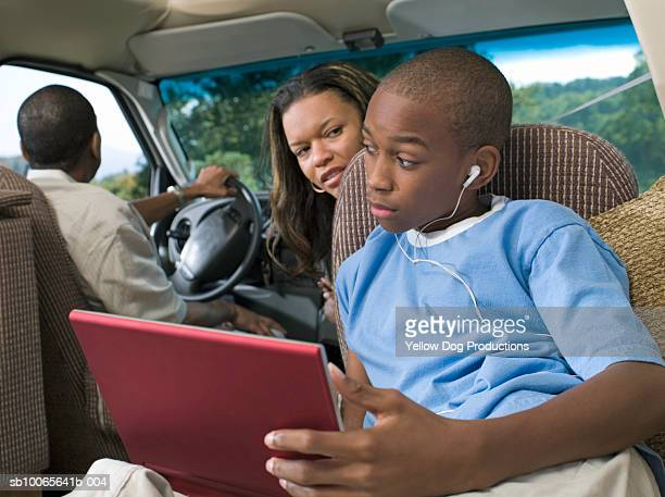 Parents with son (12-13) in motorhome, boy watching DVD player