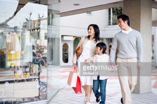 Parents with son (6-7) in shopping mall : Stock Photo