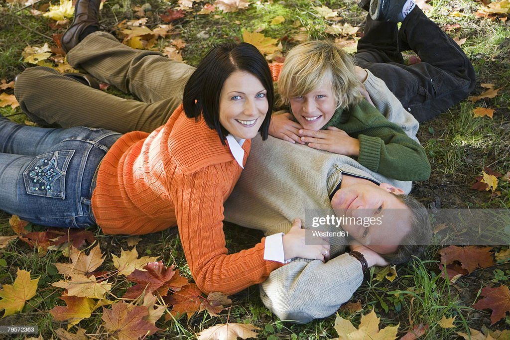Parents with son (10-12) lying in meadow, portrait, elevated view : Stock Photo