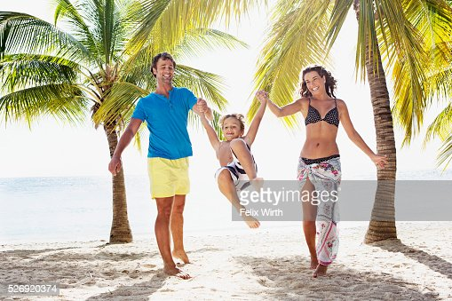 Parents with son (8-9) playing on beach : Stockfoto