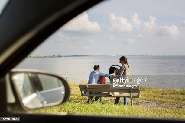 Parents with son (18-23 months) sitting on bench by sea