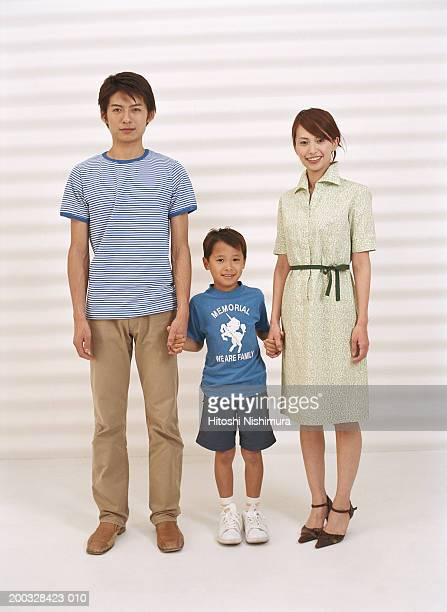 Parents with son (4-7) standing, holding hands, portrait