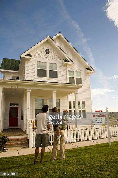 Parents with son (2-3) standing in front of Victorian house, rear view