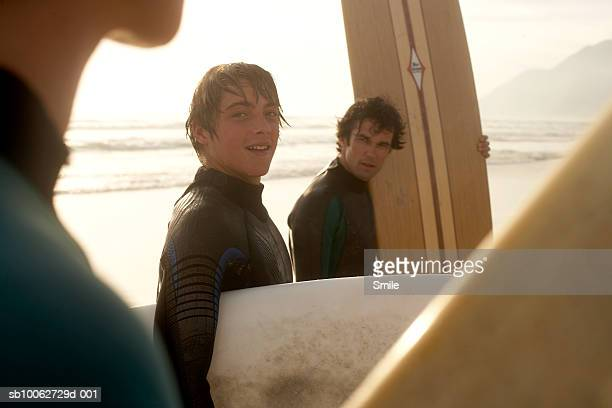 Parents with son (14-15) with surfboards on beach
