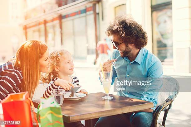 Parents with their daughter enjoy sunny day in a city.