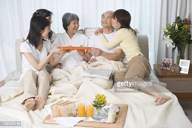 Parents with their three daughters on the bed