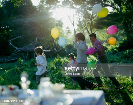 Parents with two children (6-7, 8-9) holding balloons, running through garden : Stock Photo