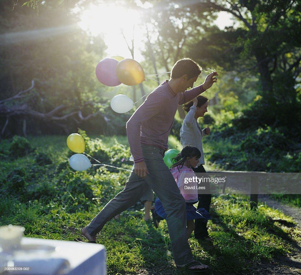 Parents with two children (6-7, 8-9) holding balloons, running through garden