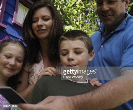 'Parents with two children (6-7, 8-9) looking at photo in garden, close-up, low angle view' : Stock Photo