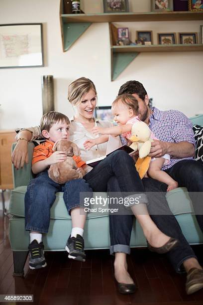 Parents with two children sitting on sofa