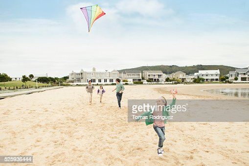 Parents with two girls (6-7), (8-9) flying kite : Bildbanksbilder