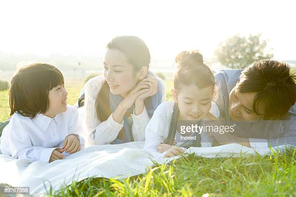 Parents with two kids lying relaxing on mat