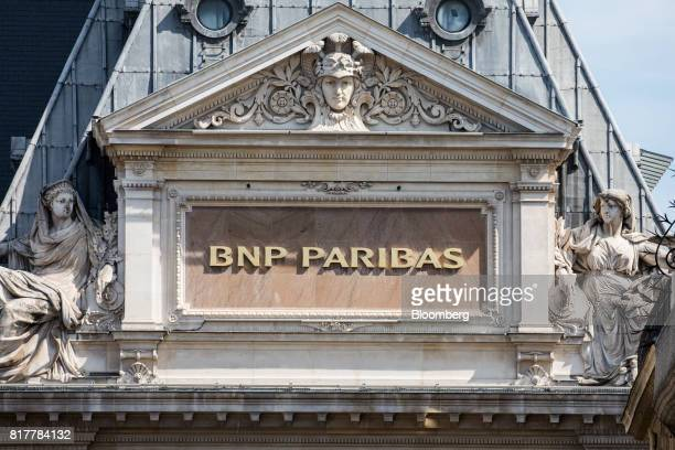 Paribas SA logo on stonework outside a BNP Paribas bank branch in Paris France on Tuesday July 18 2017 BNP Paribas agreed to pay $246 million to...