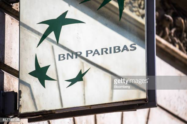 Paribas SA logo sits on a sign outside a BNP Paribas bank branch in Paris France on Tuesday July 18 2017 BNP Paribas agreed to pay $246 million to...