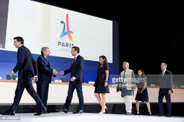 Paris 2024 Olympic bid Copresident Tony Estanguet walks past International Olympic Committee President Germany's Thomas Bach greeting French...