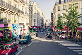Street scene around the Opera district, which is in Paris 9th Arrondissement. Apartment buildings, stores, restaurants, cars and people are visible in the image.
