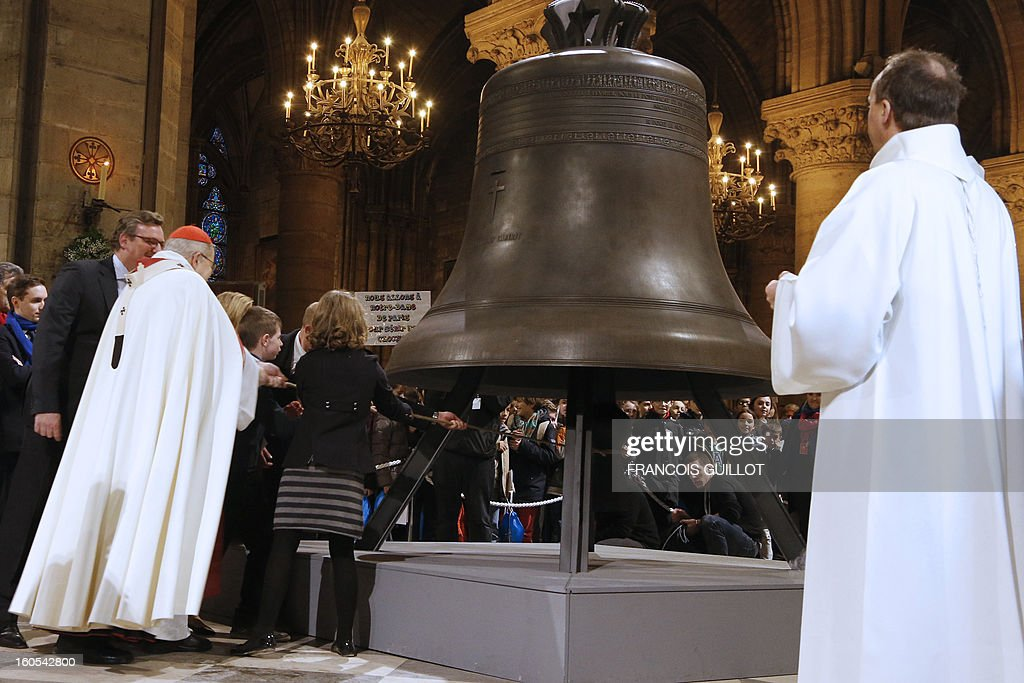 Paris Archbishop Andre Vingt-Trois and young people ring one of the new bells of Notre-Dame de Paris Cathedral during its blessing mass on February 2, 2013 in Paris. The bell on the picture, the biggest among the nine new ones, has been made in the Dutch Royal Eijbouts foundry in Asten. Baptised 'Marie,' it weighs 6 tons and plays a G sharp note (sol diese).