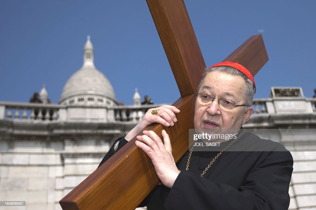 Paris' archbishop Andre Vingt-Trois carries a cross as he takes part in a Way of the Cross in Paris, in front of the Sacre-Coeur Basilica in Montmartre district, on March 29, 2013, to celebrate Good Friday. AFP PHOTO/ JOEL SAGET