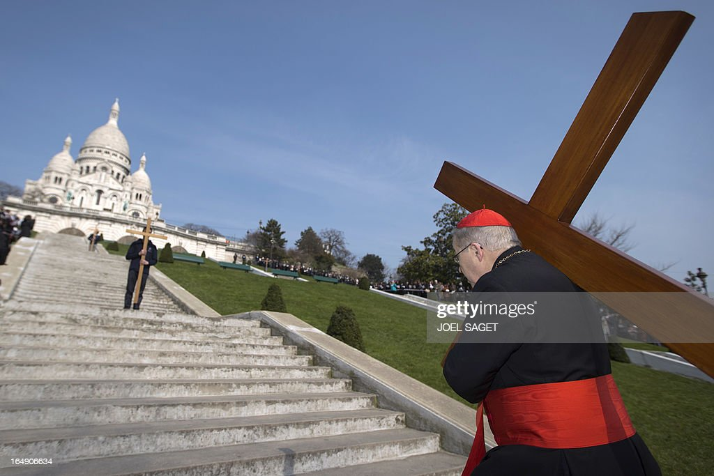 Paris' archbishop Andre Vingt-Trois carries a cross as he takes part in a Way of the Cross in Paris, in front of the Sacre-Coeur Basilica in Montmartre district, on March 29, 2013, to celebrate Good Friday.
